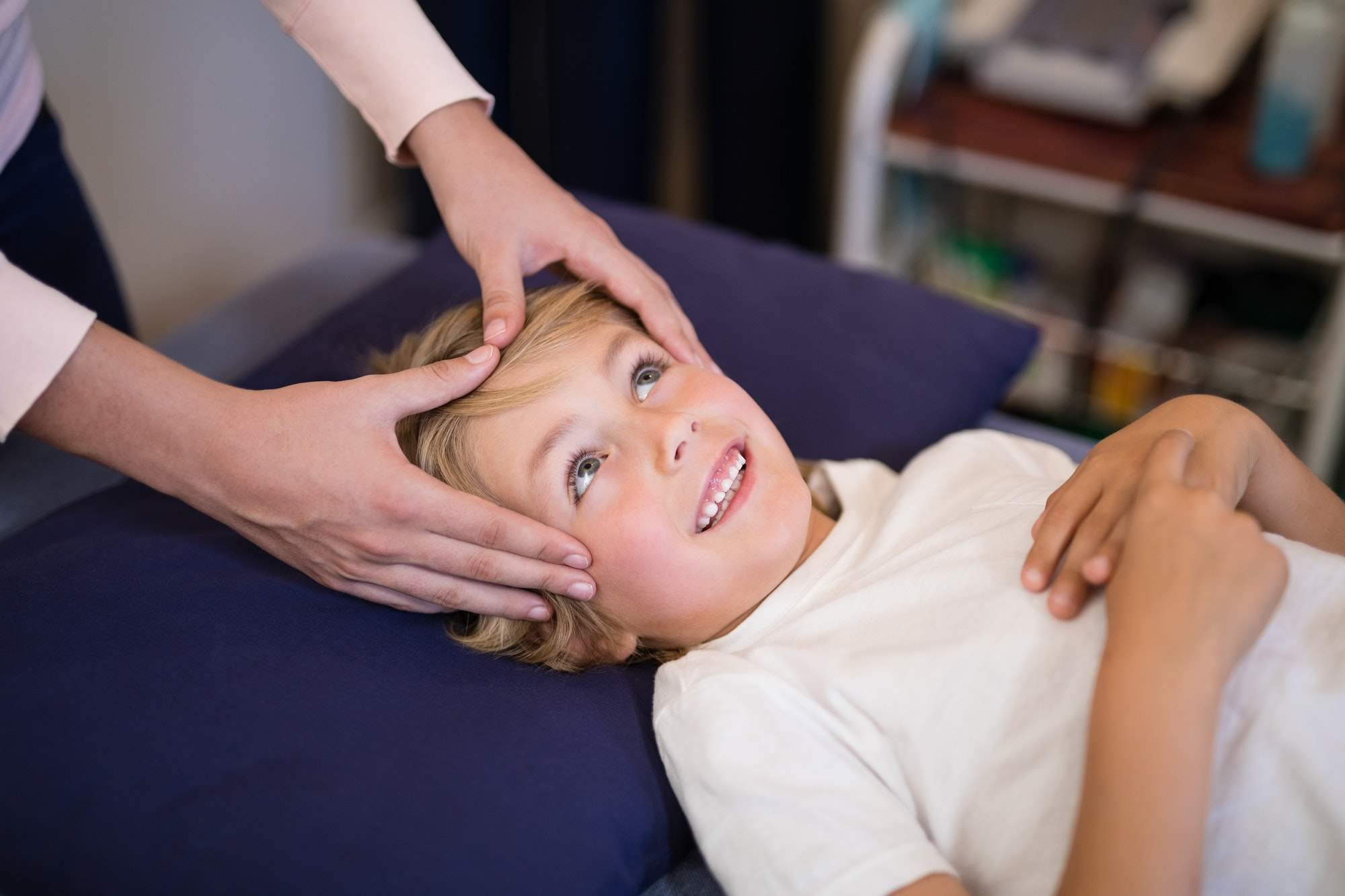 Cropped hands of female therapist giving head massage to boy lying on bed